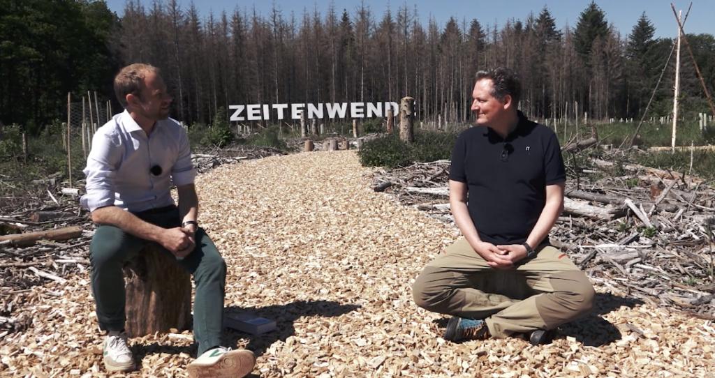 Foto von Sven Focken-Kremer von der GLS Treuhand im Gespräch mit Eckart von Hirschhausen auf einer Lichtung im Kottenforst. Im Hintergrund steht der Slogan Zeitenwende