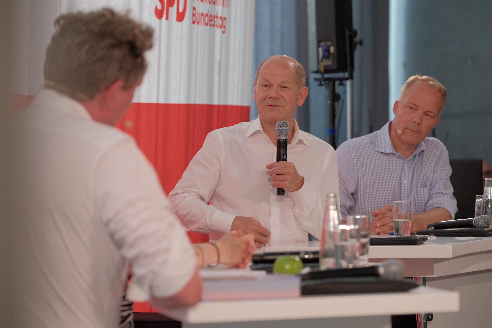 """Foto von Eckart von Hirschhausen, Olaf Scholz und Matthias Miersch beim Panel """"Auf dem Weg nach Glasgow – Sind wir noch zu retten?"""" vor SPD-Banner"""