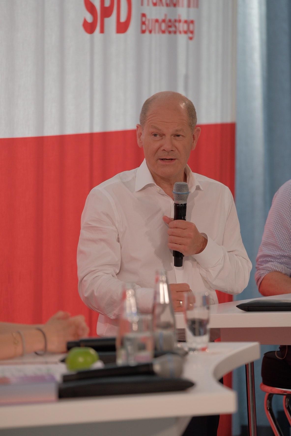"""Foto von Olaf Scholz beim Panel """"Auf dem Weg nach Glasgow – Sind wir noch zu retten?"""" vor einem SPD-Banner"""