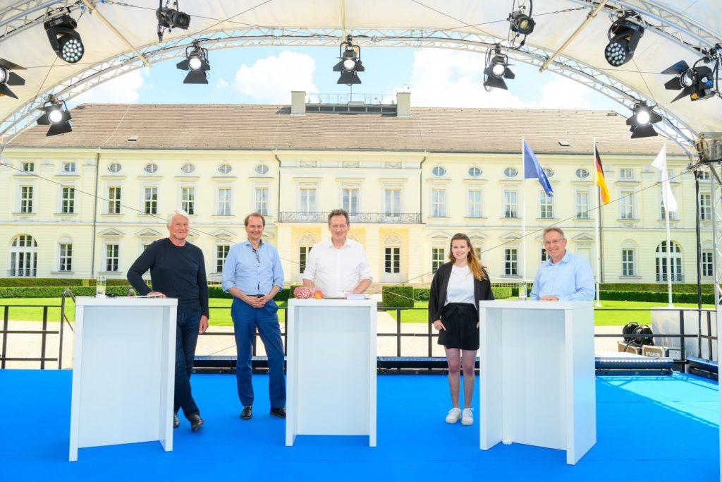 """Foto der Teilnehmenden der Podiumsdiskussion """"Deutschland 2050 – Visionen für unser Leben der Zukunft"""" auf der Woche der Umwelt 2021 vor dem Amtsitz des Bundespräsidenten."""