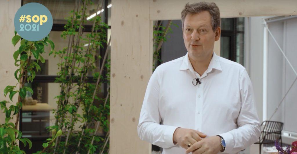 Foto von Eckart von Hirschhausen in weißem Hemd vor grüner Kulisse