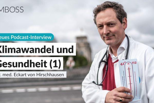 Foto von Eckart von Hirschhausen im Arztkittel mit einem symbolischen Fieberthermometer in der Hand. Im Hintergrund sieht man eine Straße und Häuser.
