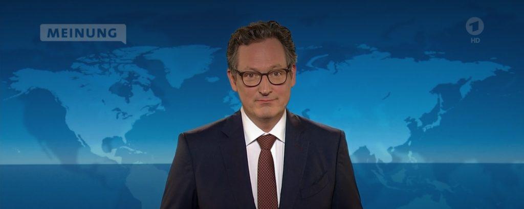 Foto von Dr. Eckart von Hirschhausen mit dunklem Anzug, weißem Hemd und roter Krawatte vor Bluescreen bei den Tagesthemen, wo er über den 6. Bericht vom Weltklimarat sprach
