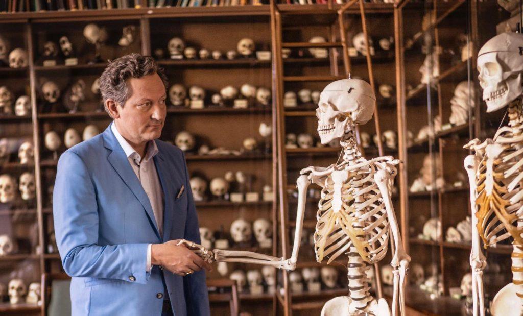 Foto von Dr. Eckart von Hirschhausen, der einem Skelett die Hand reicht.